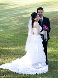 Wedding Couple-5. Wedding couple holding flower bouquet smiling in the golf course Stock Photos