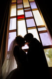 Wedding couple. Silhouette of wedding couple against stainglass window inside of church Royalty Free Stock Photo