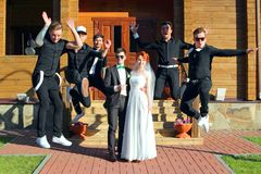Free Wedding Couple And Jumping Groom`s Friends Stock Photo - 154529920