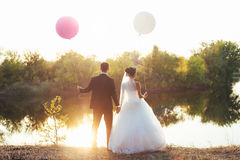 Wedding couple with balloons. A wedding couple standing on a lake coast holding balloons Royalty Free Stock Photos