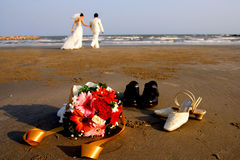 Wedding couple on beach. Husband and wife walking barefoot on a beach after their wedding royalty free stock image
