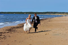 Wedding Couple on the Beach Laughing. The bride and groom barefoot on the beach by the sea are laughing and really enjoying their great day together that will Stock Photos