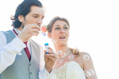 Wedding couple blowing soap bubbles outside Stock Images