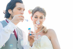 Wedding couple blowing soap bubbles outside Royalty Free Stock Images
