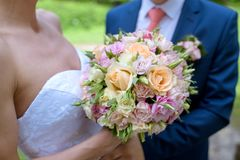 Wedding couple with bouquet. Female and male portrait. Beautiful model girl in white dress. Man in suit. Beauty bride with groom. Woman in bridal gown. Cute Royalty Free Stock Photo