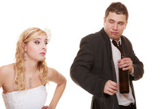 Wedding couple, bride with alcoholic drinking groom. Royalty Free Stock Photos