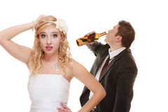 Wedding couple, bride with alcoholic drinking groom. royalty free stock image