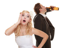 Wedding couple, bride with alcoholic drinking groom. Royalty Free Stock Photo