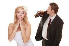 Wedding couple, bride with alcoholic drinking groom. Royalty Free Stock Photography