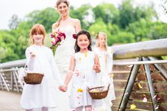 Bride in wedding dress with bridesmaids on bridge Stock Photography