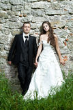 Wedding couple, stone brick wall Royalty Free Stock Photo