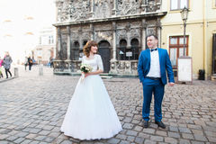 Wedding couple of bride and groom standing by old stone chapel Royalty Free Stock Image
