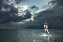 Wedding couple, bride and groom standing under threatening cloud Stock Images