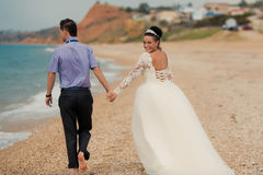 Wedding couple, bride and groom, walking on a. Wedding couple walking on a beautiful beach Stock Photography