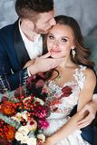 Wedding couple with bride holding bouquet. Sensual portrait of a young couple. Wedding photo indoor. Wedding couple hugging, the bride holding a bouquet of stock photo