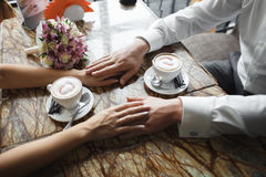 Wedding couple at cafe. Man holds woman's hand, drinks cappuccino. Bride and groom coffee break dating gift, bouquet on table Stock Photo