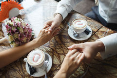 Wedding couple at cafe. Man holds woman's hand, drinks cappuccino. Bride and groom coffee break dating gift, bouquet on table Stock Photos