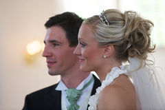 Wedding couple in church. Wedding copule in church looking at the priest Royalty Free Stock Photo