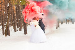 Wedding couple with color smoke in the winter park Stock Photos