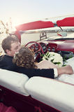 Wedding couple in convertible. Bride and groom sitting in a red convertible overlooking the ocean Royalty Free Stock Image