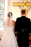 Wedding couple and cross. Wedding couple standing infront of a cross Royalty Free Stock Photo