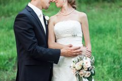 Wedding couple cuddling, nose to nose stock photography