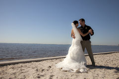Wedding couple dancing on beach. A  happy bride and groom dancing on the beach Stock Photos