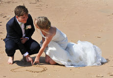 Wedding Couple drawing a Heart in the Sand. A Young Wedding Couple kneeling on the sandy beach drawing a Heart in the Sand together and when they finish their Stock Photo