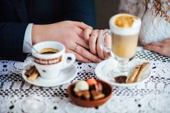 Wedding couple drink coffee and holding hands. royalty free stock photo