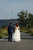Wedding couple and drone. Bride and groom walking, drone flying and filming Royalty Free Stock Image