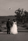 Wedding couple and drone. Bride and groom walking, drone flying and filming Royalty Free Stock Images