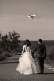 Wedding couple and drone. Bride and groom walking, drone flying and filming Stock Photo