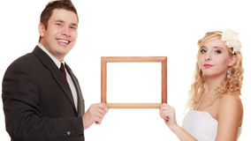 Wedding couple with empty frame for photos. Royalty Free Stock Image