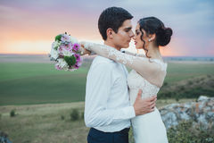 Wedding couple. In the evening. Peaceful romantic moment. Happy bride and groom on a beautiful beach on sunset. bride in a white dress holding a bouquet of royalty free stock photos