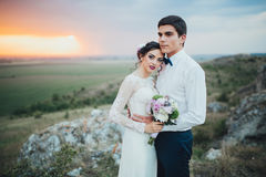 Wedding couple. In the evening. Peaceful romantic moment. Happy bride and groom on a beautiful beach on sunset. bride in a white dress holding a bouquet of royalty free stock photo