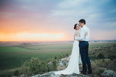 Wedding couple. In the evening. Peaceful romantic moment. Happy bride and groom on a beautiful beach on sunset. bride in a white dress holding a bouquet of stock images