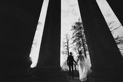 Wedding couple faces the sun standing behind the pillars.  Royalty Free Stock Photo