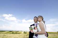 Wedding couple on the field. Young attractive wedding couple posing on a green field against blue sky royalty free stock photo