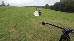 Wedding couple in field backstage video shooting with camera crane stock video