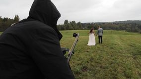 Wedding couple in field backstage video shooting with camera crane stock footage