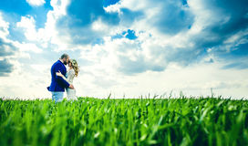 Wedding couple in the field with green grass stock image