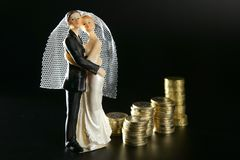 Wedding couple figurine and golden coins Royalty Free Stock Photo