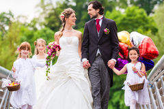 Wedding couple with flower children on bridge Stock Photography
