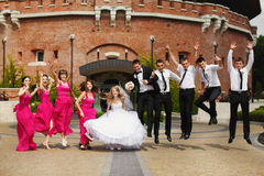 Wedding couple and friends have fun jumping in the front of an o Royalty Free Stock Photography