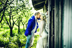 Wedding couple in the garden near wooden wall Royalty Free Stock Image
