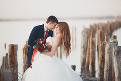 Wedding couple, groom, bride with bouquet posing near sea on sunset.  Royalty Free Stock Photos