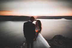 Wedding couple, groom, bride posing near sea on sunset.  Royalty Free Stock Photos