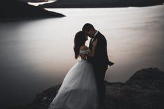 Wedding couple, groom, bride posing near sea on sunset.  Stock Photo