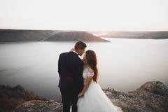 Wedding couple, groom, bride posing near sea on sunset.  Stock Photography