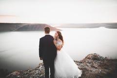 Wedding couple, groom, bride posing near sea on sunset.  Stock Image